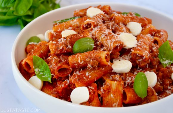 One Pot Pasta with Italian Sausage in white bowl with mozzarella, Parmesan and fresh basil