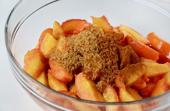 Sliced peaches with brown sugar and cinnamon in clear bowl