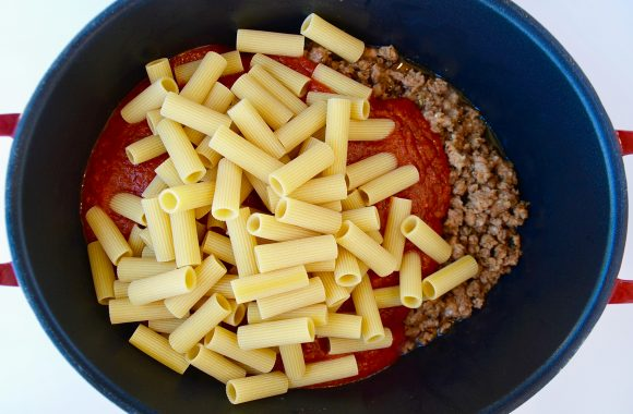 Uncooked noodles in pot with marinara sauce and cooked sausage