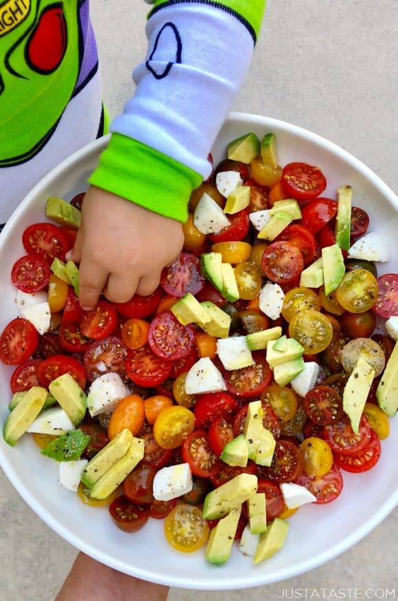 A white bowl containing cherry tomatoes and avocado with a little boy's hand reaching into it