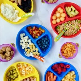 Various plates of kid food ideas with a child's hand reaching into one