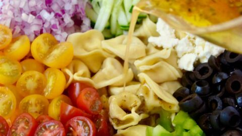 Dressing being poured into bowl containing Greek Tortellini Pasta Salad ingredients