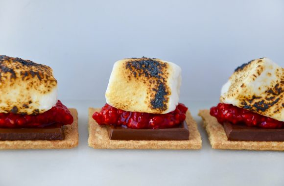 Three toasted marshmallows on graham crackers with fresh raspberries