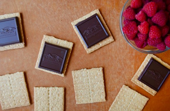 Graham crackers, chocolate and raspberries on a cutting board