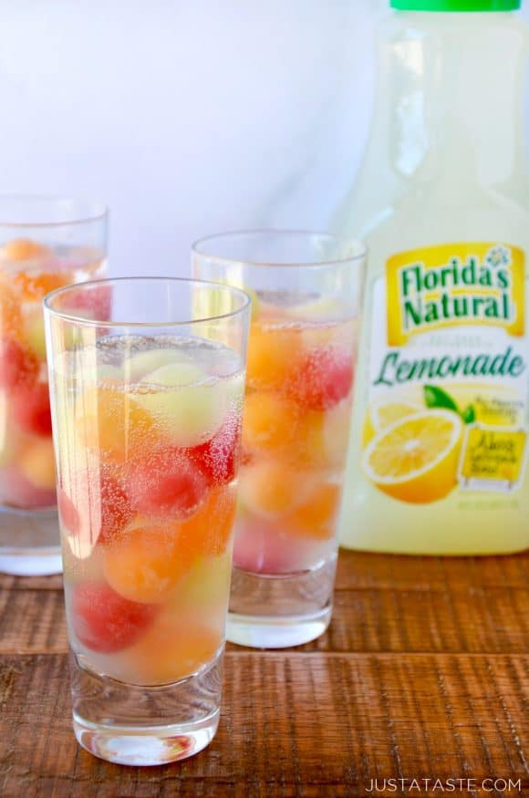Clear cocktail glasses with melon balls and a bottle of lemonade