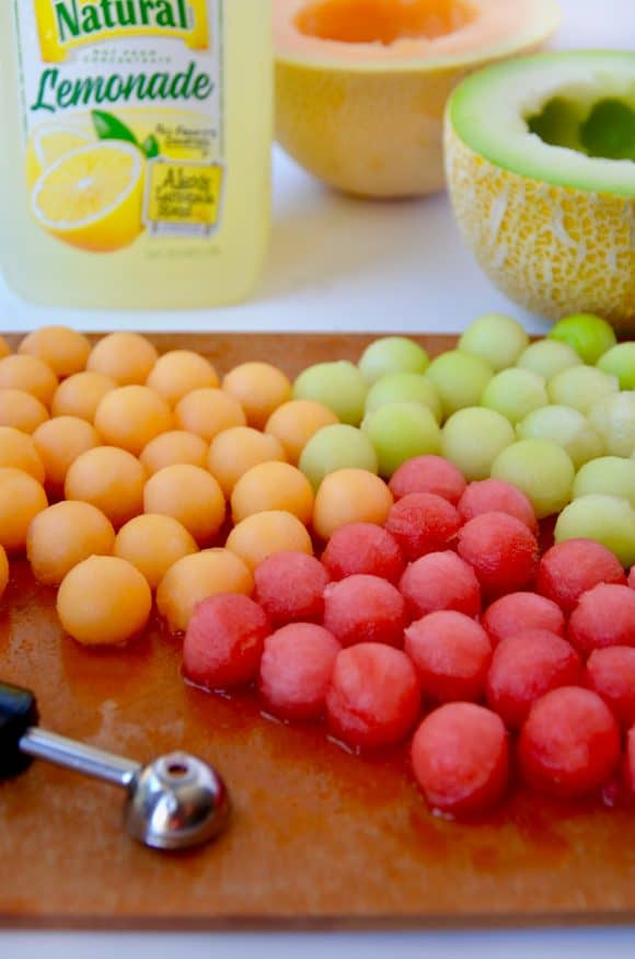 Melon balls on a cutting board with lemonade in the background