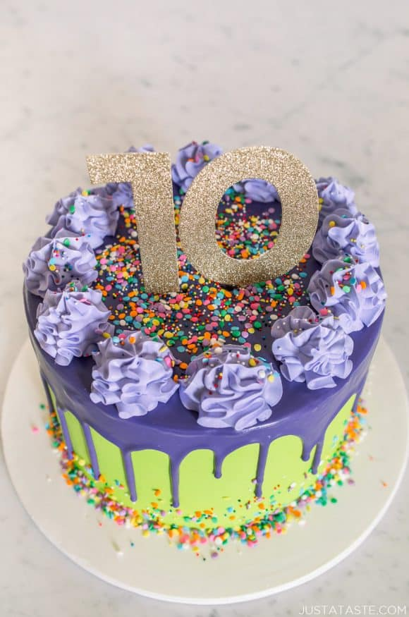 A purple and green 10-year anniversary cake with drips and sprinkles