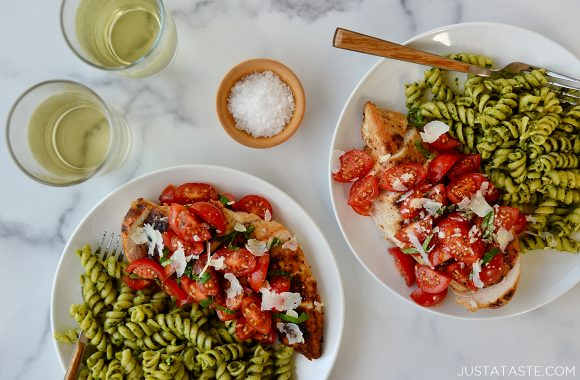 Two plates containing easy bruschetta chicken and pesto pasta