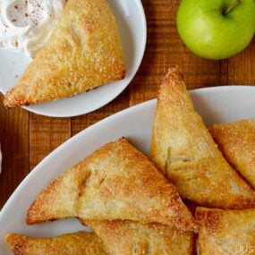 Easy Apple Turnovers on serving plate next to a small bowl with whipped cream