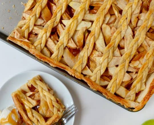 A caramel apple slab pie with a piece cut out