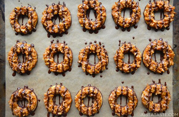 A baking sheet filled with rows of homemade Samoas Girl Scout cookies drizzled with chocolate