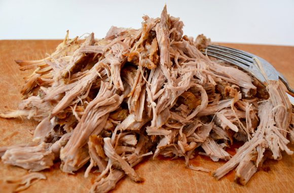 Pile of pulled pork with fork on cutting board