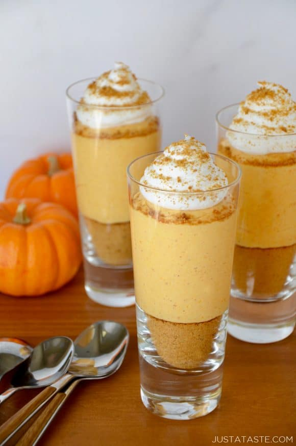 Spoons next to No-Bake Pumpkin Cheesecake Parfaits topped with whipped cream