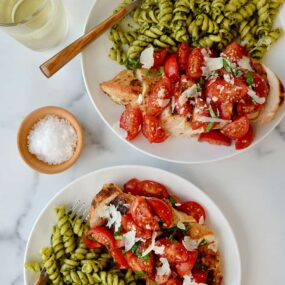 Two plates containing Quick Bruschetta Chicken and pesto pasta next to glasses filled with wine
