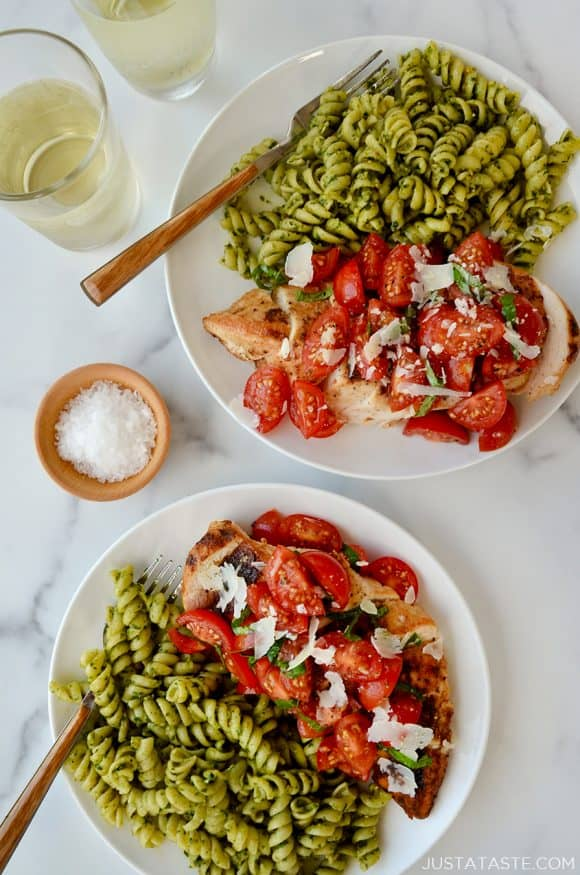 Two plates containing chicken breasts topped with tomatoes and pesto pasta next to glasses filled with wine
