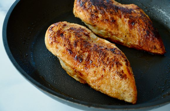 Seared chicken breasts in nonstick skillet