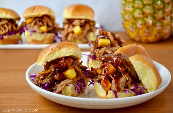 Slow Cooker Hawaiian Pulled Pork with purple cabbage on buttery buns atop a white plate