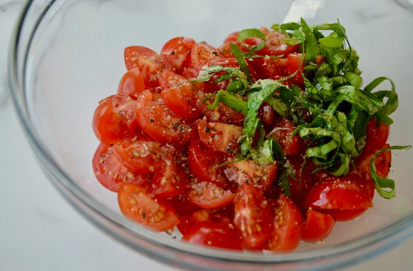 Bowl containing cherry tomato salad with fresh basil and cracked pepper