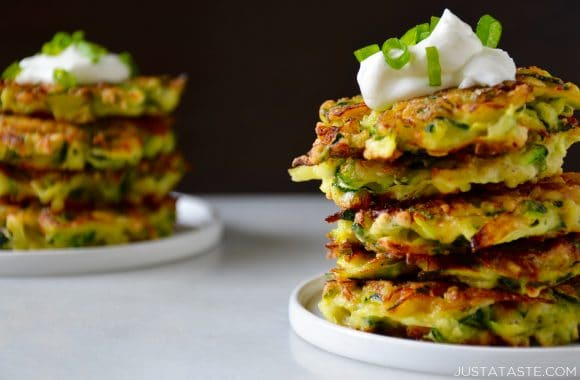 Two white plates containing stacks of zucchini fritters topped with sour cream