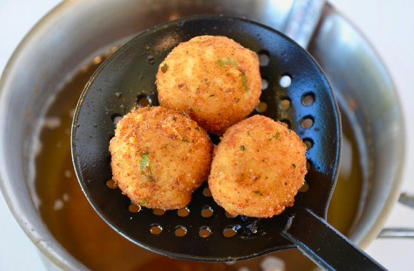 Fried Leftover Mashed Potato Balls in slotted spoon above pot of oil