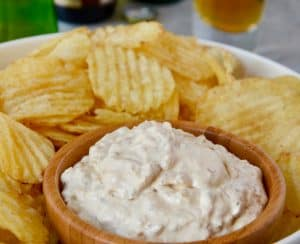 Homemade Sour Cream and Onion Dip with potato chips on serving tray