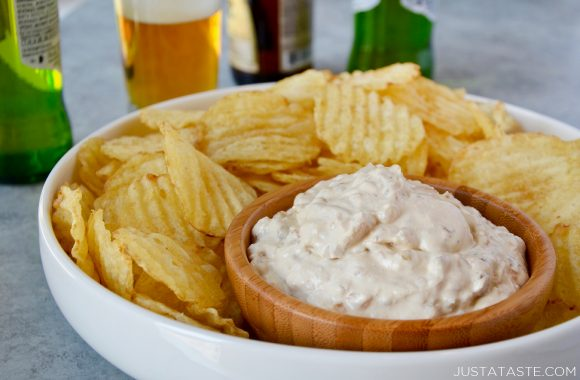 Homemade Sour Cream and Onion Dip in small bowl surrounded by potato chips in serving tray