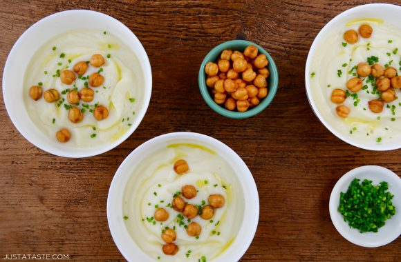 Three bowls with Quick Cauliflower Soup topped with roasted chickpeas and fresh herbs