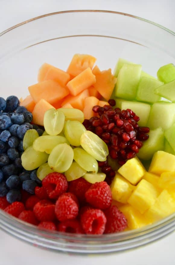 A glass bowl containing fruit salad separated by fruit