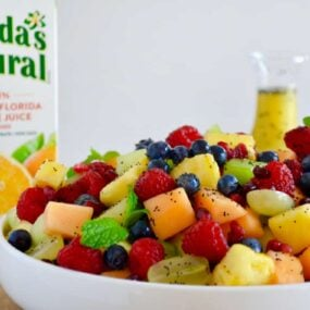 A white bowl with fruit salad and a carton of orange juice in the back