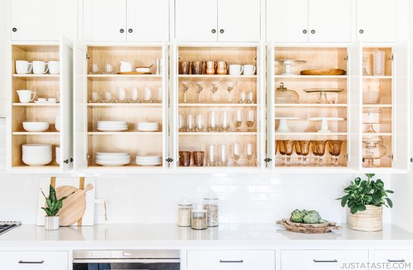 White cabinets filled with plates, cups and bowls all lined up