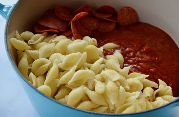 Closeup view of Conchiglie, marinara sauce and pepperoni in large blue stockpot