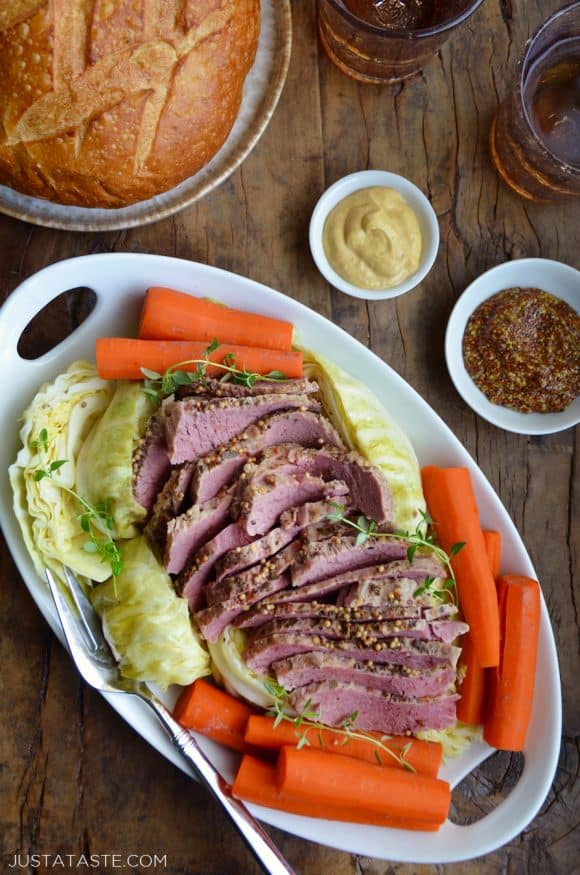 White plate containing The Best Slow Cooker Corned Beef and Cabbage with carrots next to a loaf of bread and two small bowls containing mustards