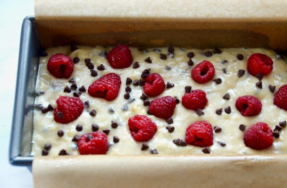 A loaf containing banana bread batter topped with raspberries and chocolate chips