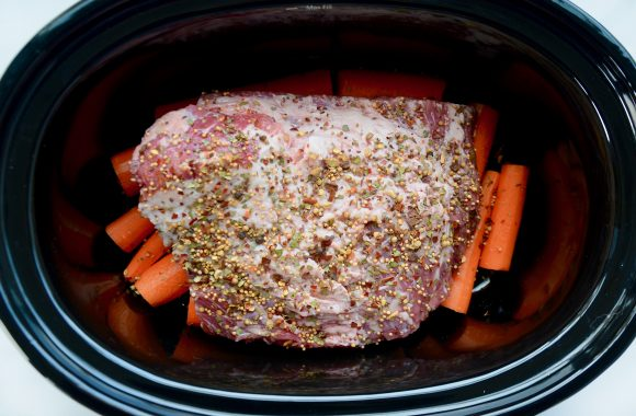 Top view of slow cooker containing corned beef brisket on top of carrots