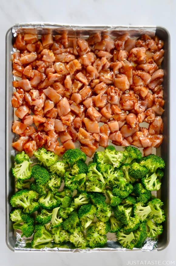 Foil-lined baking sheet with diced chicken thighs and broccoli florets