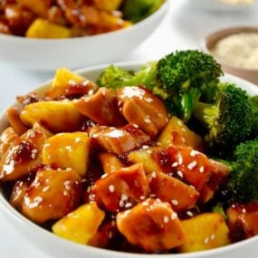 White bowl containing Sheet Pan Pineapple Chicken and Broccoli garnished with sesame seeds