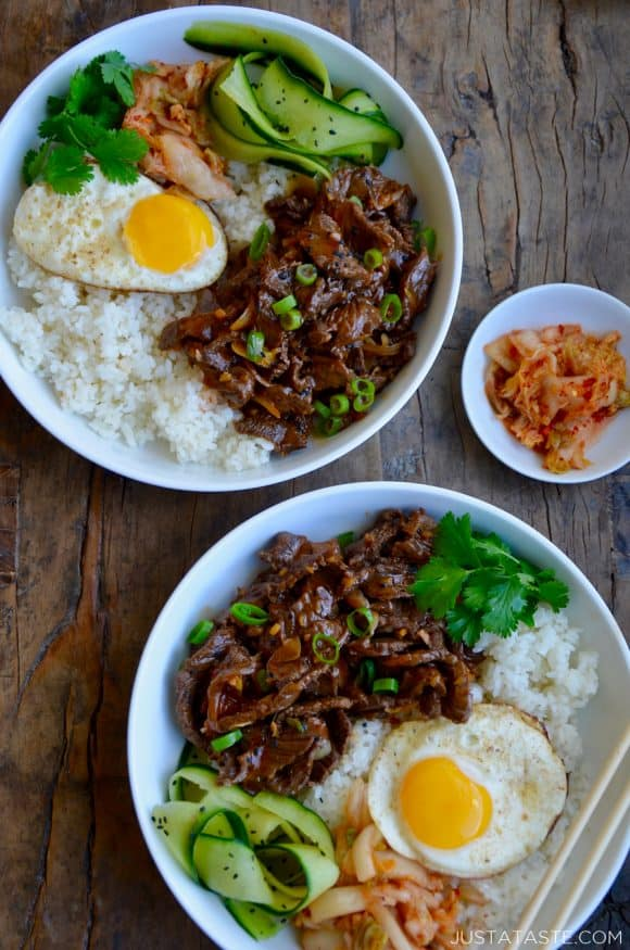 Top down view of two bowls containing easy beef bulgogi, white rice, a fried egg, cucumber ribbons, fresh cilantro and kimchi