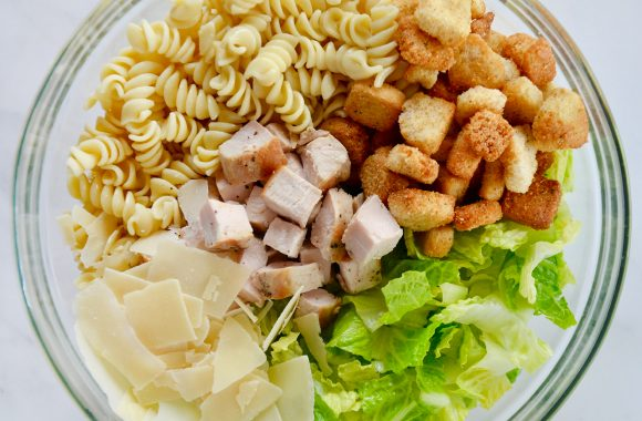 Glass bowl containing the best Chicken Caesar Pasta Salad ingredients
