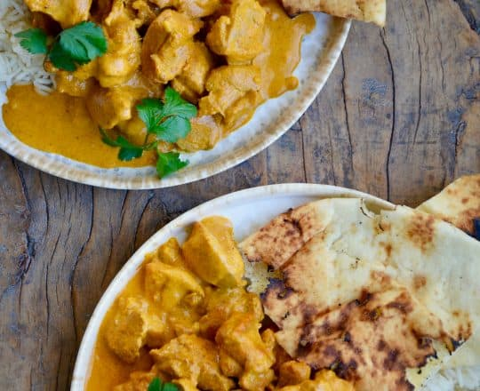 Two plates containing The Best Chicken Tikka Masala with cilantro, white rice and naan