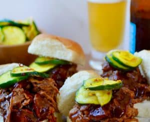 White buns piled high with Instant Pot Barbecue Pulled Pork and pickles in front of a bottle and glass of beer