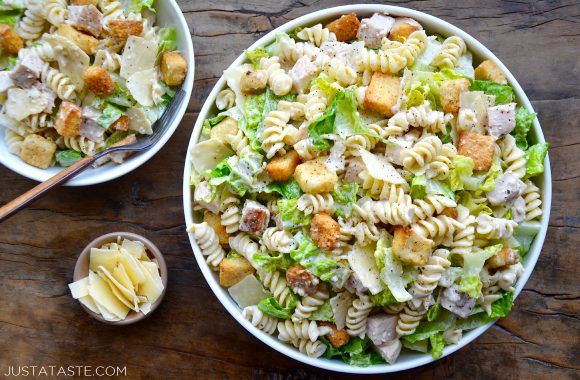 A top down view of a large bowl and a small bowl containing Chicken Caesar Pasta Salad