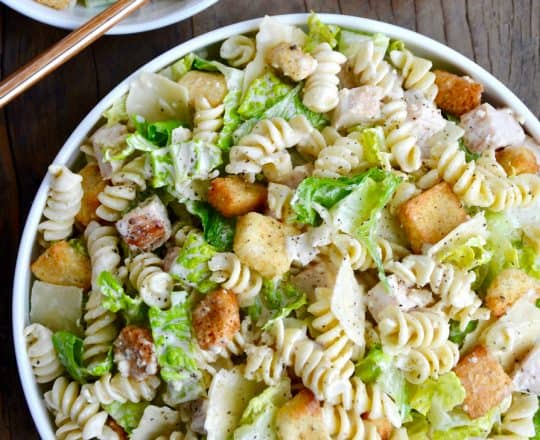 A top down view of a bowl containing the best Chicken Caesar Pasta Salad