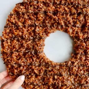A top down view of a Giant Samoas Cookie Cake with a female hand touching it