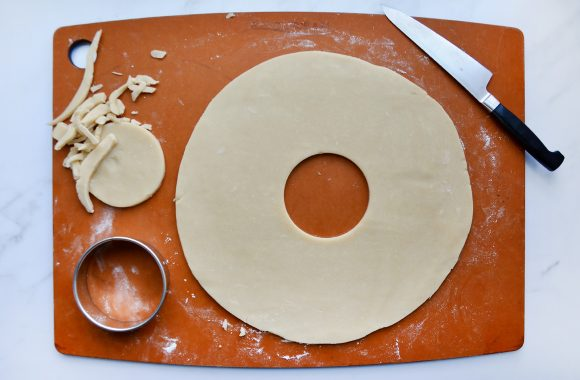 Cutting board with round cookie cutter, samoas cookie dough and knife