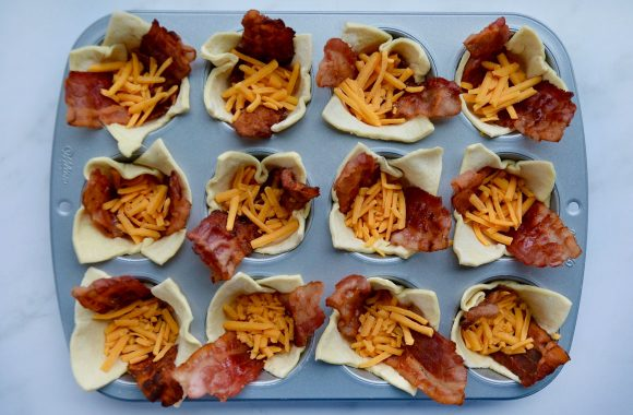 Muffin tin containing puff pastry filled with bacon and shredded cheese
