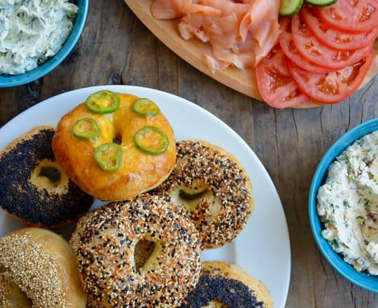 A white platter with homemade bagels surrounded by a lox platter and three bowls of cream cheese