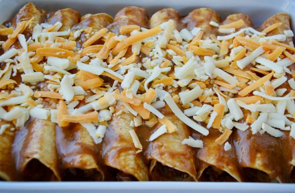 A baking pan filled with chicken enchiladas topped with cheese
