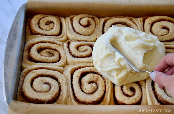 Spreading cream cheese frosting over easy homemade cinnamon rolls