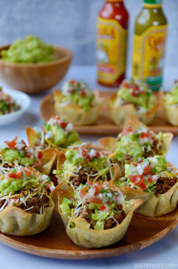 Easy Taco Salad Cups on a wood serving plate with hot sauce and guacamole in background