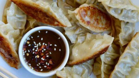 Pork Potstickers with Citrus-Soy Dipping Sauce on white plate with chopsticks